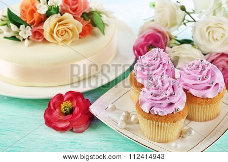 Cake with sugar paste flowers and cupcakes, on light background poster