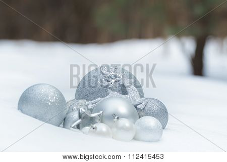 Silver grey shiny Christmas ornaments with reindeer on snowy ground at winter forest background