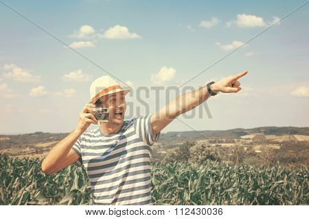 Man with the old camera pointing with the finger
