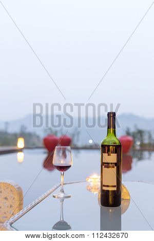 redwine and cup on table near pond in gloomy sky