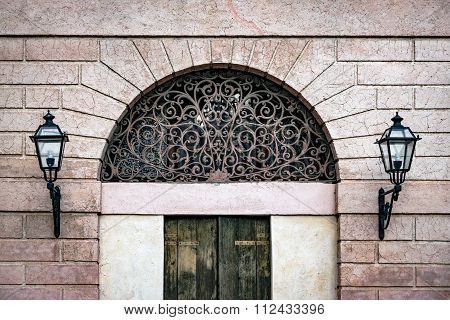 Facade Of An Ancient Italian Villa With Artistic Iron Grill.