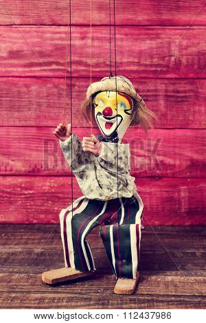an old marionette with its face painted like a clown being manipulated on a red rustic wooden surface
