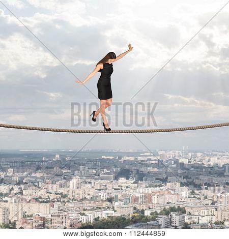 Businesslady walking on rope