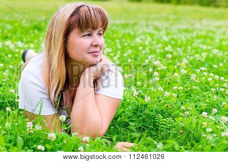 50-year-old Woman On A Green Meadow Looking To The Side