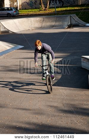 Joung Red Haired Boy Jumps With His Bike At The Skate Park