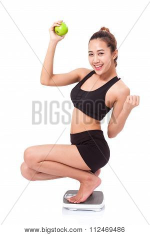 Women on scale cheering for achieving her weight loss goal and green apple.