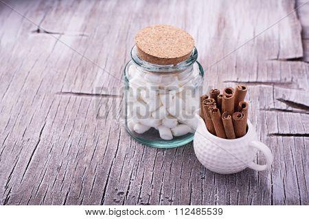 Cinnamon sticks in bucket on wooden background