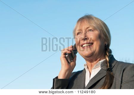 Happy mature businesswoman using cellphone.