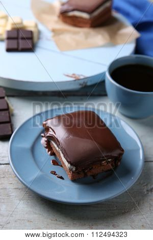 Delicious chocolate brownie on plate on wooden background