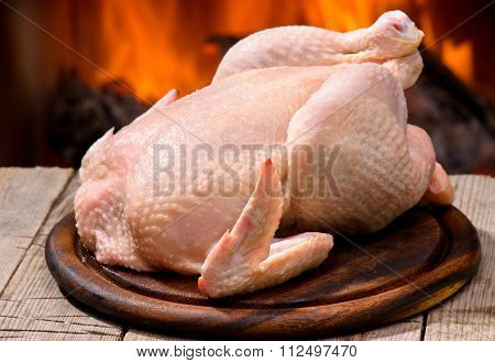 Raw chicken on a background of fire.