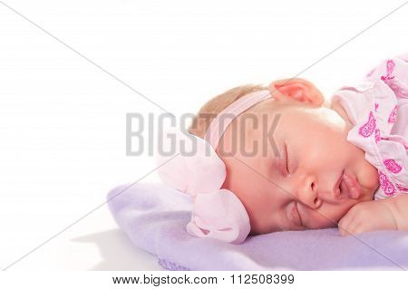 Newborn baby girl slipping on her tummy