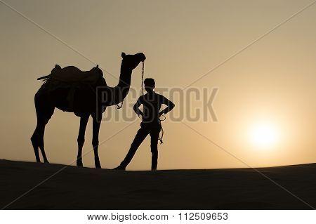 Silhoutte Of Camel Boy Crossing In The Thar Desert.