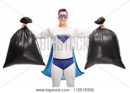 Superhero in a white and blue costume holding two trash bags and looking at the camera isolated on white background