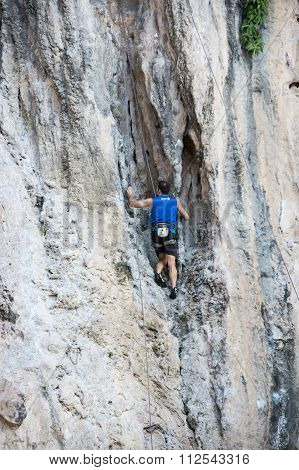 A Man Climbing Up A Steep Limestone Cliffs