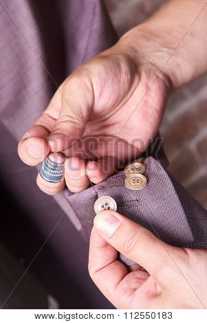dressmaker sews a button on jacket