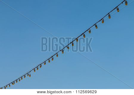 Closeup Of The Hanging Light Bulbs With Blue Sky 1
