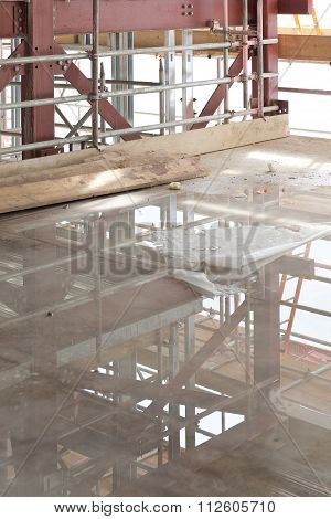 A Construction Site With Concrete Slab With Water Puddle And Scaffolding