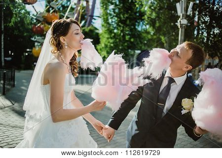 newlywed happy funny couple walking in the amusement park with cotton candy