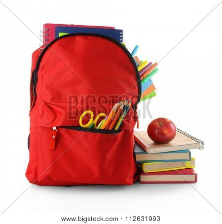 Red backpack with colourful stationary and pile of books with an apple on the top isolated on white background