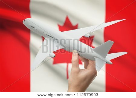 Airplane In Hand With Flag On Background - Canada