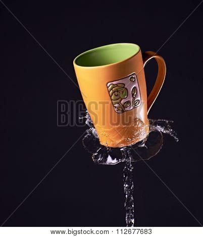 orange/green mug in mid air