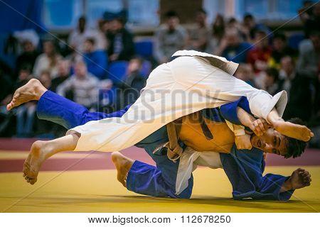 wrestling duel between athlete men judokas on tatami