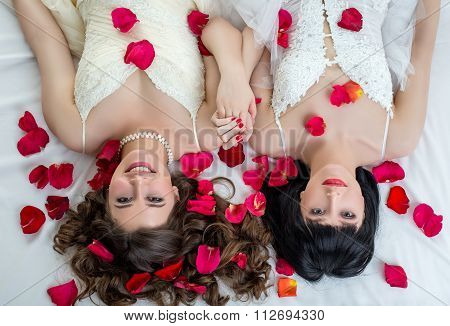 Top view of two charming brides looking at camera