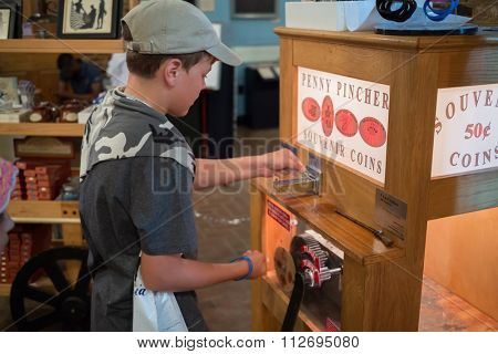 USA, PHILADELPHIA - 02 SEP, 2014: Little boy (with model release) is making souvenir with the penny pincher.