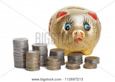 Golden piggy bank with stacked coin in front of white background
