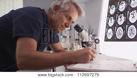 Middle Aged Male Radiologist Looking Through Microscope