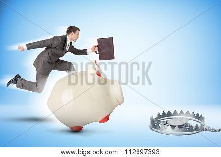 Businessman running forward with piggy bank