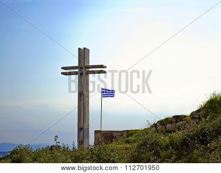 big wooden cross with the greek flag