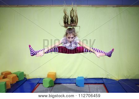 Girl is jumping high in striped tights on the big trampoline.