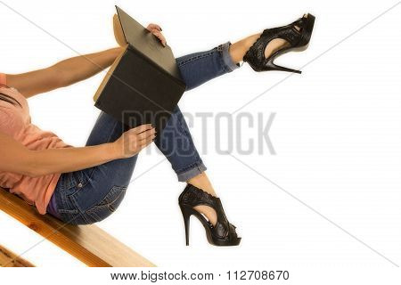Woman Legs In Denim Jeans And Black Heels Reading A Book