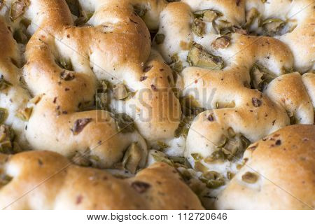 The focaccia is a traditional loaf - bread from the Italian cuisine and this is closely related to the pizza. in this picture you can see the texture and the spices that made this delicious food. also you can see pieces of green olives and black. poster