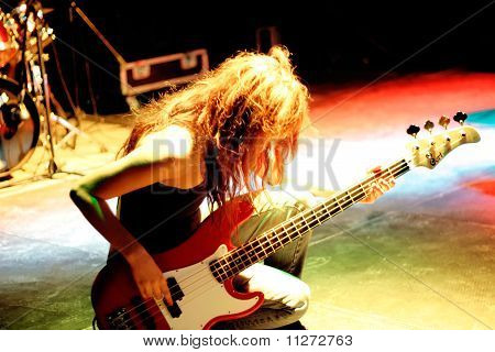 Female bass player playing guitar on stage
