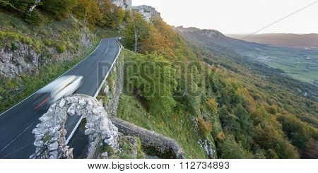 Car driving up mountain with curved road