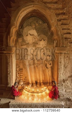 Bagan, Myanmar - Feb 20, 2015: Southeast Asian Young Little Buddhist Monks Praying With Candle Light