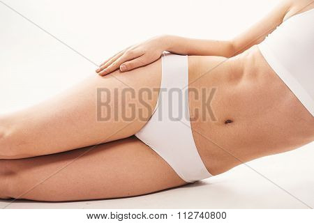 Woman In White Underwear Lying On Her Side On White Background While Her Hand On A Tip. Isolated On