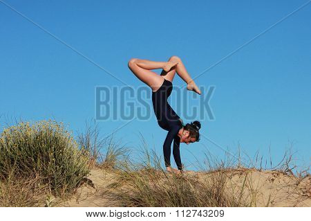 Gymnast Doing Acrobatic Handstand On The Beach