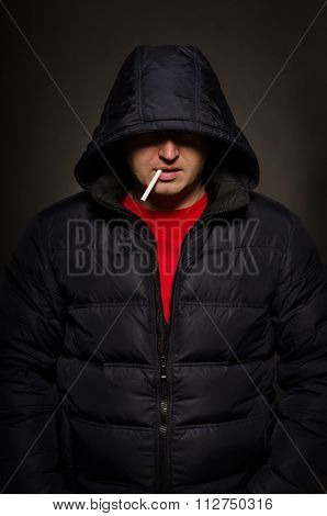 Portrait of a man in a hood with a cigarette