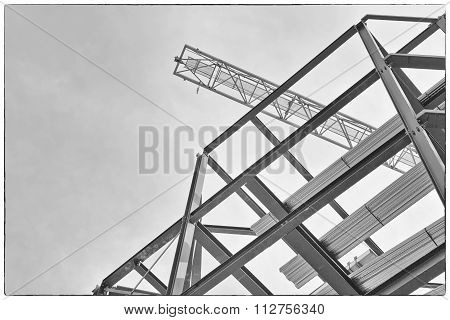 A Construction Site With Steel Framing And A Yellow Construction Crane