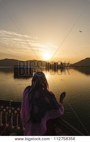 A women feeding a fish in The palace Jal Mahal at sunrise.