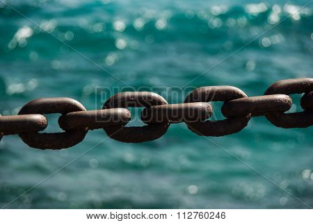Rusty Boat Anchor Chain In Front Of Ocean