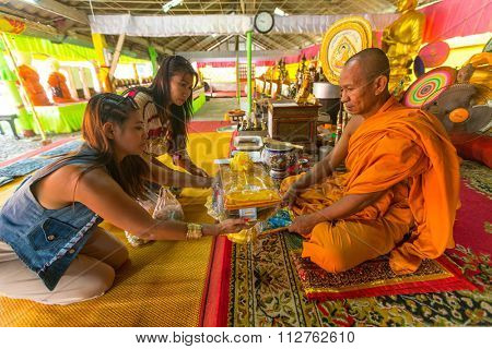 KOH CHANG - THAILAND - DEC 29, 2015: Unidentified local women give offerings to monks in the Wat Khlong Prao monastery. Ko Chang one of the largest Islands of Thailand, located of 310 km from Bangkok.