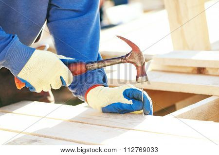 Joinery and carpentry. A closeup of male carpenter worker hands hammering nail into board outdoors