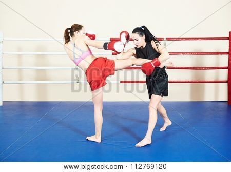 Thai kickboxing match. Muay thai female boxers fighting at training boxing ring