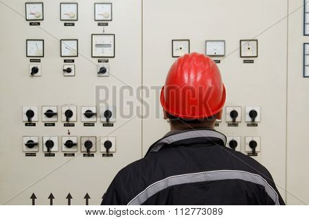Technician With Red Helmet Reading Instruments Power Plant Control Center