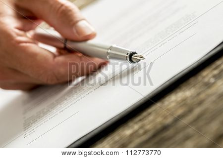 Closeup Of Male Hand Holding An Ink Pen Pointing With Its End On A Line In The Bottom Of A Contract