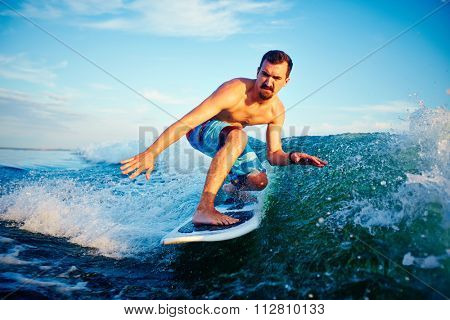Surfer boy on his surf board in blue water